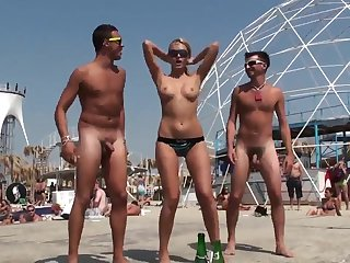 Naked guys on the beach have fun with a young girl
