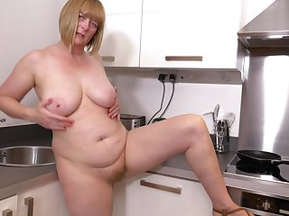 Mature slut April takes off her clothes in the kitchen to play